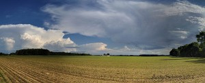Panoramic image of Spring Clouds swirling over a freshly planted field in Cranbury, NJ